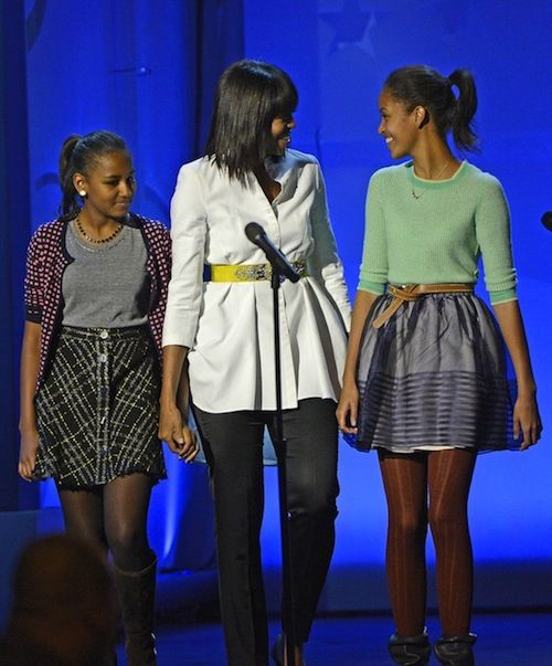 The First Lady & First Daughters, Sasha, & Malia, attended the Kids' Inaugural Concert at the Walter E. Washington Convention Center in Washington, D.C. The concert paid special tribute to military spouses & children, with appearances expected from Alicia Keys, John Legend, Katy Perry, Smokey Robinson, Stevie Wonder & others. Mrs. Obama's white tunic appears to be the same Alexander McQueen piece that the first lady wore in 2011.