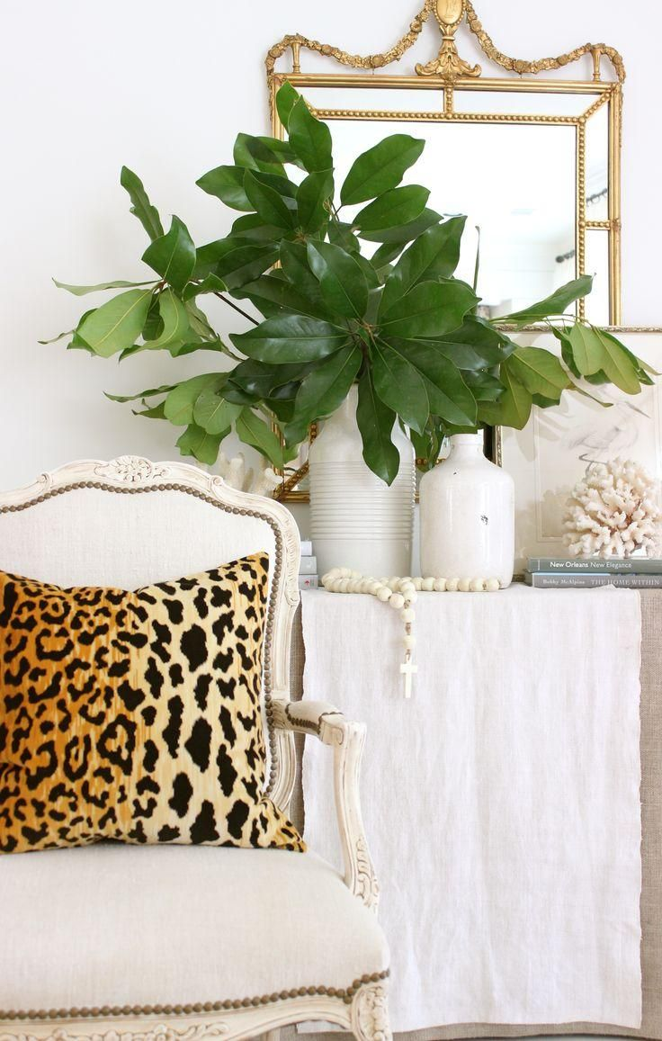 All white room accented with bright fresh greenery and a leopard throw pillow -- love this mix of contemporary and traditional styles!