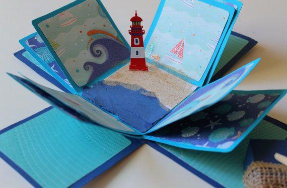 Scatola- biglietto per festeggiare chi ama il mare e lestate o per chi vuole conservare i ricordi delle vacanze. Su ogni aletta, infatti, si possono attaccare foto, biglietti di concerti o cinema allaperto, oggettini, insomma souvenir delle vacanze estive appena trascorse da regalare a chi si ama o ad unamica speciale.  E realizzata a mano con cartoncino da 300gr e applicazioni in carta per scrapbooking, e sabbia applicata al centro insieme al piccolo faro in 3D.  Tutti i dettagli sono stati…