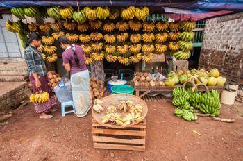 vendor: Thanlyin, Myanmar - March 14, 2011: The Myanmar vendor selling banana and coconut at street market  in Thanlyin, Myanmar.