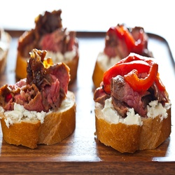 Flank Steak With Goat Cheese On Toast. The flank steak is marinated in red chili flakes, smoked paprika, olive oil, salt and pepper. Toppings included goat cheese, roasted red bell peppers and a balsamic fig and onion jam.
