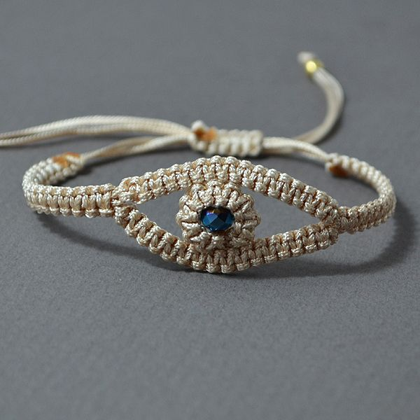 """Handmade macrame bracelet  """"small blue eye"""". Its made out of a beige waxed thread  and a small blue pearl, which is in the center of the bracelet. The bracelet is adjustable so it can fit to a wide variety of sizes."""