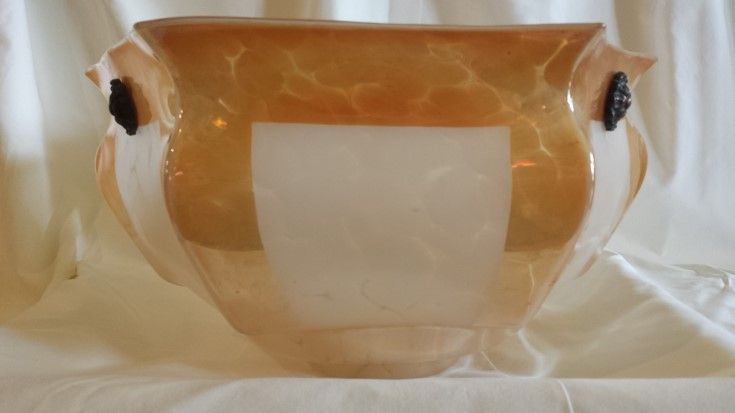 This is different. Dish, glass light with a lustre glaze in dappled peach. It attaches to the ceiling via three chains mounted on to the dark fittings seen above. Measures 36cms wide x 22cms at deepest. Cost $160 NZD