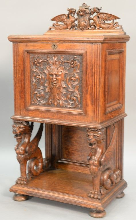 R. J. Horner Victorian oak safe cabinet having carved winged griffins back splash, carved face on door with winged griffin supports on base with round feet, interior having painted Herring & Co. New York safe Realized Price $12,000.00