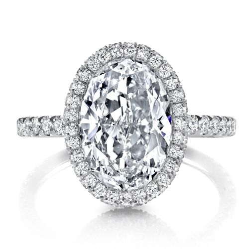 Victoria is a custom engagement ring set with an Oval cut diamond inside a…