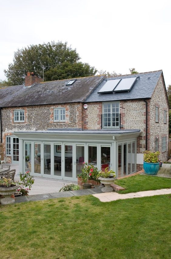 A beauty of a garden room; the soft blue-grey paintwork blends well with the attractive brick and flint.