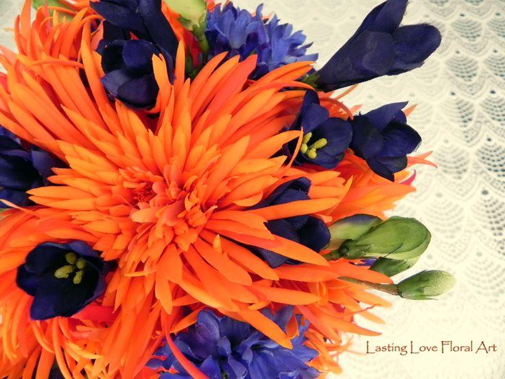 Orange real touch mums and silks in blue make this stunning bouquet pop!  #blueandorangewedding #blueandorangeweddingflowers #orangeandbluewedding #orangeandblueweddingflowers #orangeandbluebouquet #blueandorangebouquet #orangewedding #bluewedding #weddingflowers