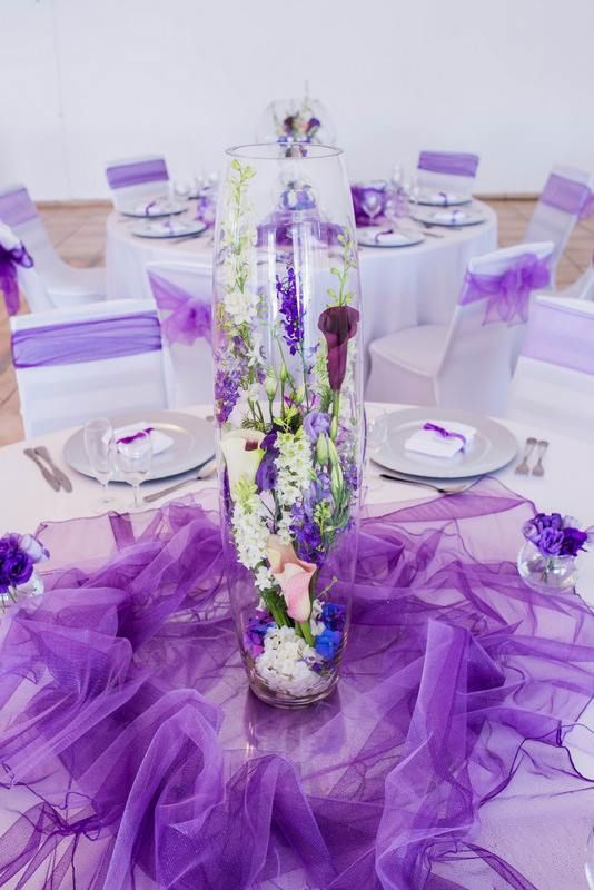 Monte Vista Venue purple centerpiece with a mix of flowers inside the bullet vase, white pebbles at the bottom of the vase, all on a round mirror and purple net.