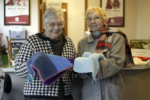 Bellevue residents Shirley Nicholls, left, and Janet Martin, right, are knitting and crocheting small blankets for cats at the Seattle Humane Society.