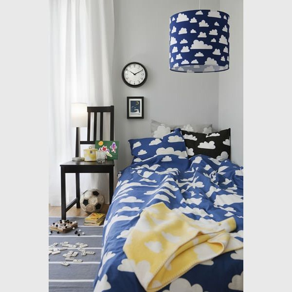 swedish fabric company farg and form fabric collection dark blue bedding a black pillow and lamp shade and a yellow blanket all with a white cloud