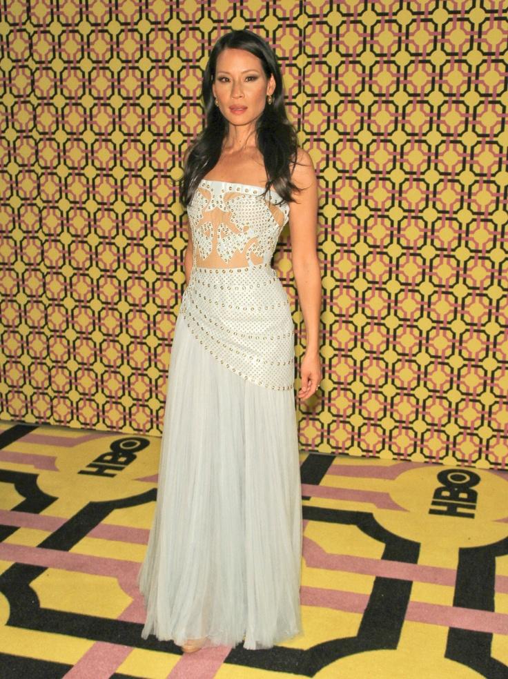 Lucy Liu  ebben a jégkék színű, arany szegecsekkel díszített Atelier Versace ruhában jelent meg az Emmy-díjátadó after partiján, amelyhez arany Jimmy Choo 'Tube' clutch-ot és 'Dalmen' platform szandált választott.forrás:instyle.hu