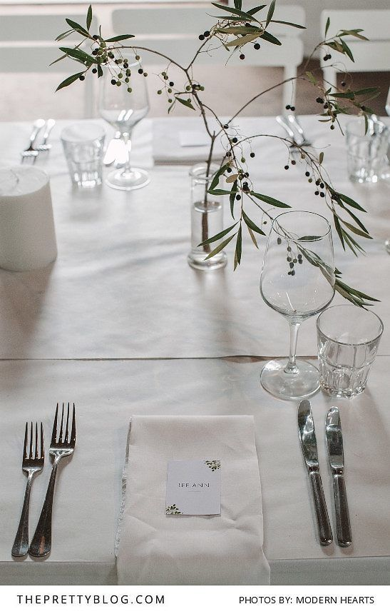 White table cloth with simple name cards and branches as centerpieces…