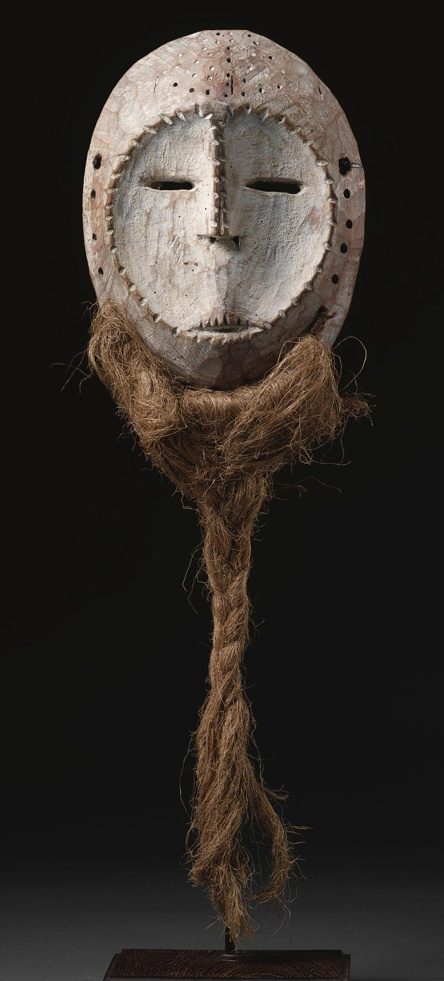 A LEGA MASK, DEMOCRATIC REPUBLIC OF THE CONGO  of oval form, and pierced around the rim for the attachment of a fiber beard, with concave heart shaped facial plane, slit mouth and raised linear nose flanked by pierced slit eyes; aged patina with traces of kaolin.  height 9 1/2 in. 24.1 cm