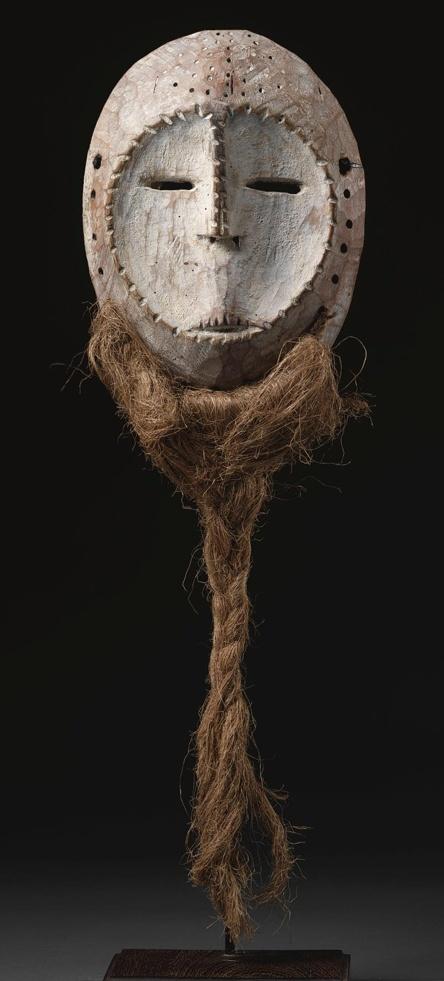 UNA MÁSCARA LEGA, REPÚBLICA DEMOCRÁTICA DEL CONGO de forma ovalada, y fueron traspasados por el borde de la unión de una barba de fibra, con el plano de la cara en forma de corazón cóncava, cortaron la boca y la nariz plantearon lineal flanqueado por perforadas ojos rasgados; pátina envejecida con restos de caolín. altura 9 1/2 pulg. 24,1 cm