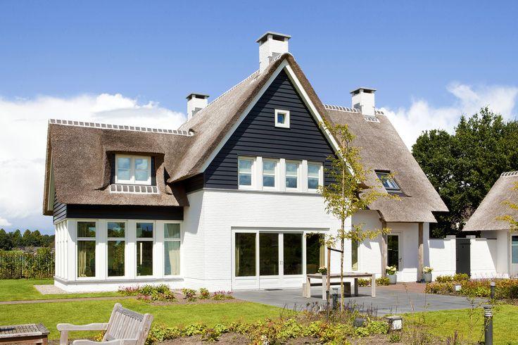 klassiek landhuis | een rietgedekt landhuis dat licht en luchtig van opzet is met wit gekeimde gevels, kozijnen en erker benadrukt door de donkergrijze potdekseldelen en buitenluiken