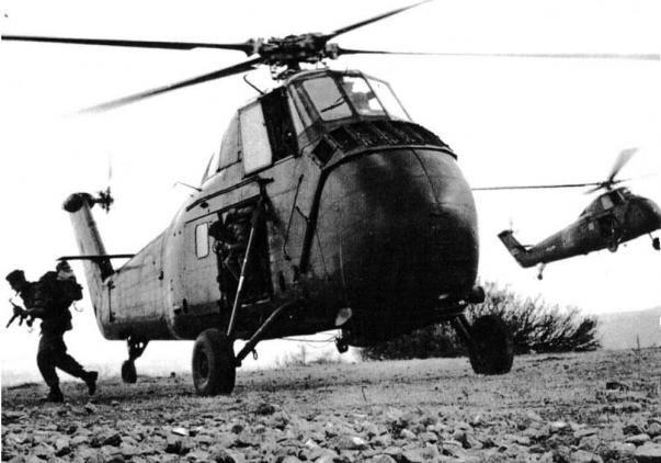 Très belle photo représentant des parachutistes qui sortent d'un hélicoptère pour une intervention militaire, lors de la guerre d'Algérie.