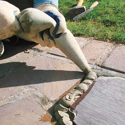 How to Repair Stone Walkway Mortar. Fill it up and smooth it out even with the flagstones.