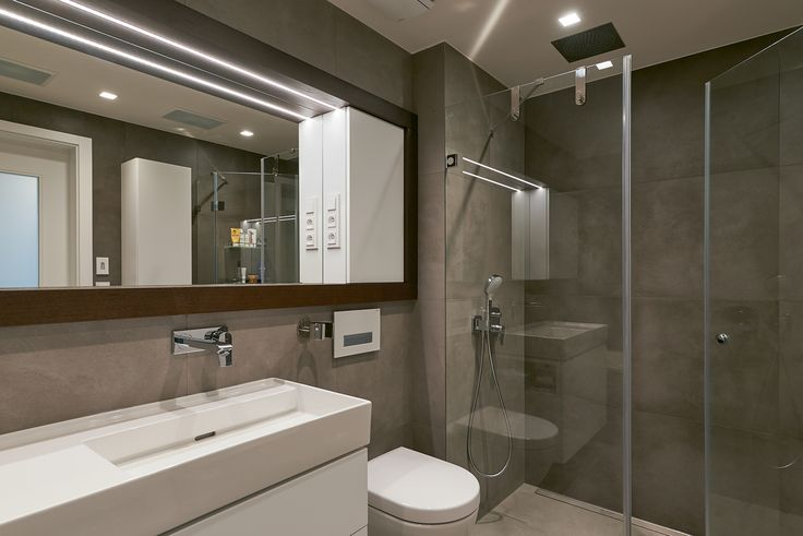 minimalisic bathroom with large built in mirror and cabinet