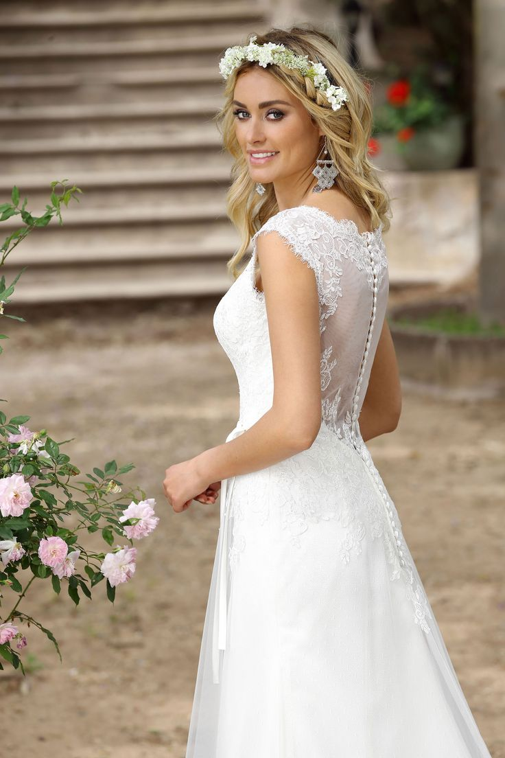 Ladybird 416019, collectie 2016 Een hele geschikte trouwjurk voor een bruid met een voorkeur voor romantiek en eenvoud. Het lijfje heeft een V-hals, de nog lagere uitgesneden rug is bedekt met doorzichtige organza bezet met kant. De soepel vallende rok heeft een klein sleepje. Een smal lint maakt de jurk af.