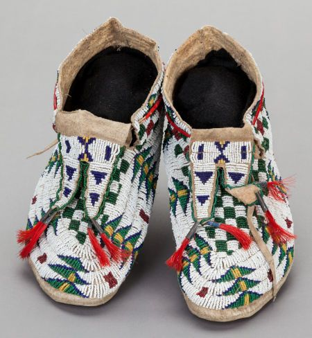 A PAIR OF SIOUX BEADED HIDE MOCCASINS. c. 1890.                                                                                                                                                      More