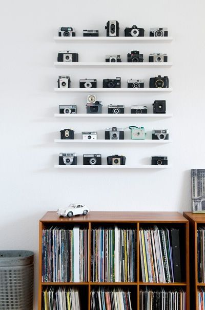 This image was really cool, I loved the clean cut layout of this image. How the shelves of the camera's are set so perfectly in the centre of the white wall, the desk/cupboard at the bottom adds an element to the image that makes it more interesting. The collection of camera's have been laid out so beautifully and perfectly spaced, the gap on the second shelf leads the viewer to wonder: is that camera being used to take the photograph? - KW:
