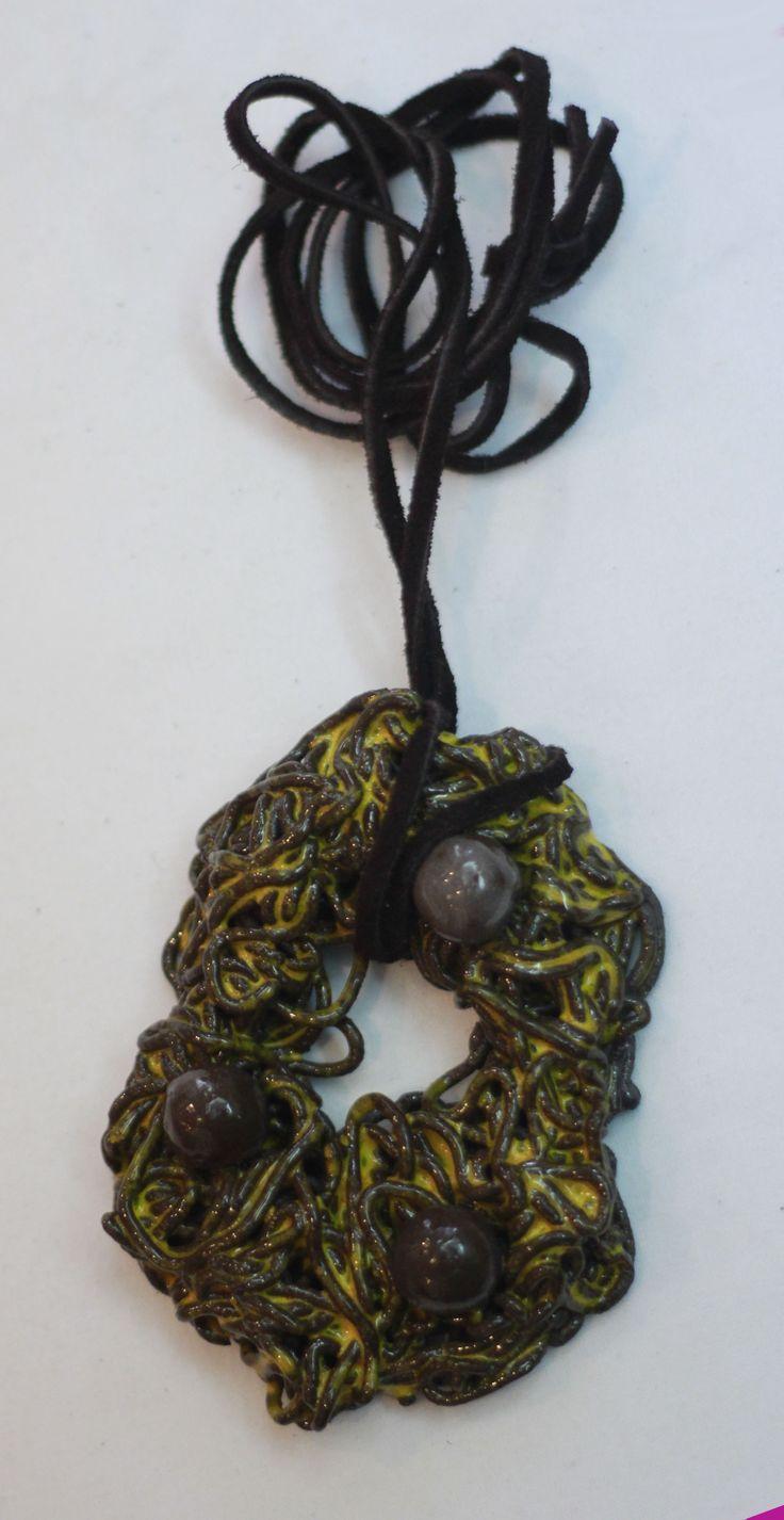 Siyah seramik çamurundan hazırlanıp, sarı sırlanmış seramik kolye. Kayışı siyah deridendir.