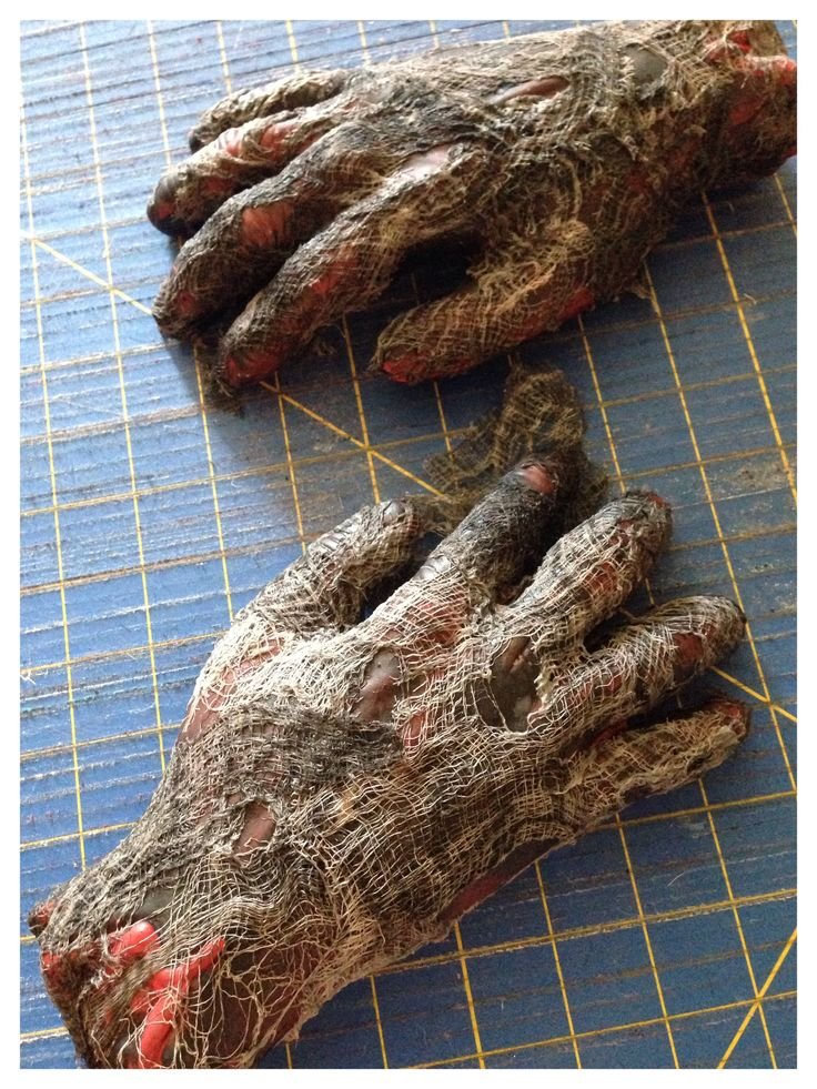 I made these zombie hands by painting them black then gluing creepy cloth to them, making sure to have some of it hang loose off of the hand. Next wash red, black & taupe paint on the hands to add dimension. Spray with a sealant so they'll stay nice for years to come! Made by Sinister Sisters for our Bubbles & Boos Bash 2014.