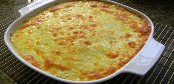4 colheres de sopa de manteiga  - 4 colheres de sopa de farinha de trigo  - 1 cebola grande ralada  - 6 gemas  - 6 claras em neve  - 1 Kg de peito de frango cozido em tempero a gosto  - 4 xícaras de chá de caldo de galinha  - 3 xícaras de chá de leite quente