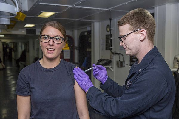 Hospital Corpsman 3rd Class Bradley Proctor, from Bossier City, Louisiana, administers an immunization shot to Intelligence Specialist 3rd Class Kaitlyn Smiddy, from Castle Rock, Colorado, aboard the amphibious assault ship USS Kearsarge (LHD 3).