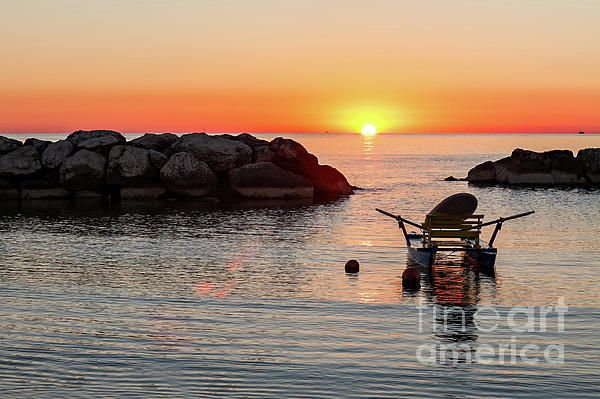 Pedalo moored in the sea during the sunrise on a clear and colorful summer morning