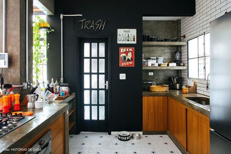 Cozinha industrial tem parede pintada de preto, piso com pastilhas em formato hexagonal, subway tiles e neon.