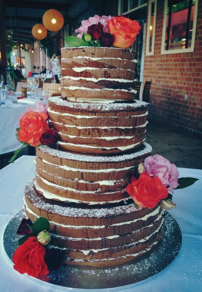A beautiful 4 tier nake layer cake with bright florals for a wedding lunch by the river.