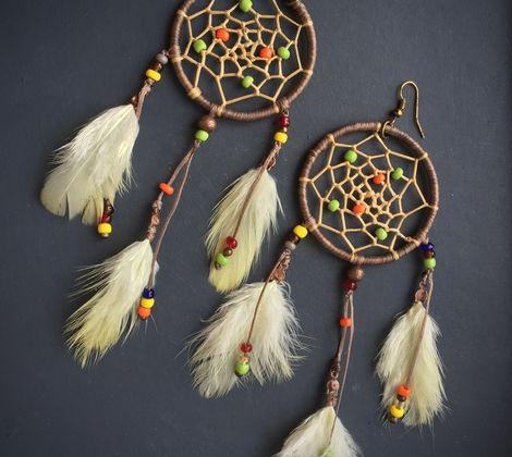 Легкие яркие серьги в бежевой гамме с бисером и натуральными перьями .  Серьги-оберег (ловец снов - защита от злых духов в индейской мифологии) выполнены в природных оттенках. Металлическая основа оплетена бежевыми вощеными нитями, а в паутинку вплетены яркие бусинки.  Перья закреплены на вощеных нитях и при движении они будут развиваться, придавая серьгам воздушность.