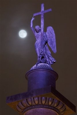 The full moon rises among the clouds behind a statue of an angel fixed atop the Alexander Column at Palace Square in St.Petersburg, Russia, late Monday, Jan. 9, 2012. (AP Photo/Dmitry Lovetsky)