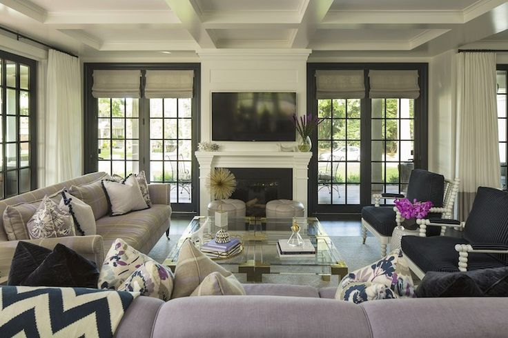 Stunning living room with black French doors dressed with linen roman shades on either side of a traditional white fireplace accented with millwork paired with black surround finished with flat screen TV above.