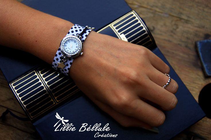 Montre nuit étoilée. Montre argentée ronde montée sur un bracelet en tissu blanc à pois bleu nuit. Une grosse étoile argentée est suspendue au cadran tandis que deux petites étoiles sont enfilées sur un cordon imitation daim de couleur bleue nuit.  Fermoir mousqueton et chaînette couleur argent.