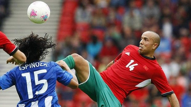 Morocco's Zouhair Feddal, right, challenges Honduras's Roger Espinoza for the ball.
