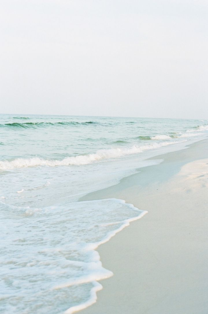 A light gray-blue sky, white sand beach, pale aqua water edged in seafoam…