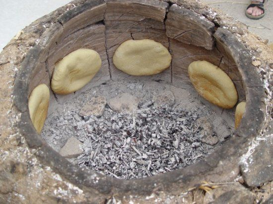 Tunisian bread is baked on the hot walls of the fire pit or oven.