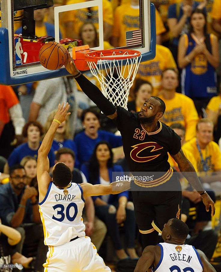 Cleveland Cavaliers forward LeBron James (R) blocks a shot attempt by Golden State Warriors guard Stephen Curry during the second quarter in Game 7 of the NBA Finals on June 19, 2016 in Oakland, California. / AFP / Beck Diefenbach