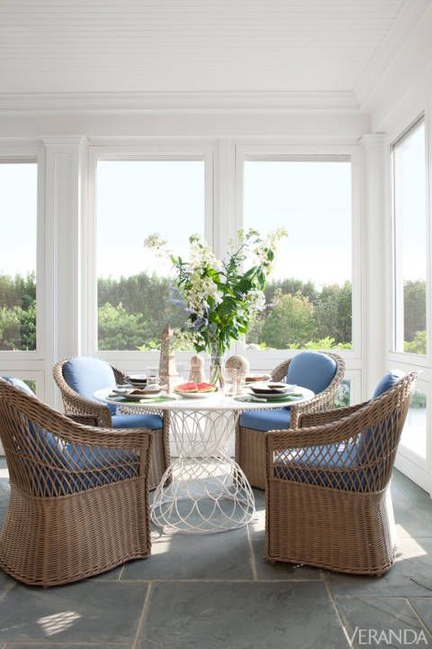 """The couple wanted an elegant space that was welcoming and livable, in a palette of blues and whites."" Wolf avoided what might have been a nautical cliché by layering in both modern and patinated elements. Comfort and user-friendliness were critical--this is very much a family space. The couple has two children, two grandchildren, and other relatives who often visit. ""They're always entertaining,"" says Wolf. Table, Emu. Vintage wicker chairs in Dedon fabric."