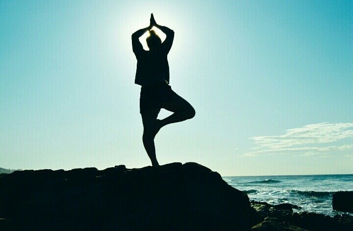 Meditation and yoga on a cliff at the beach