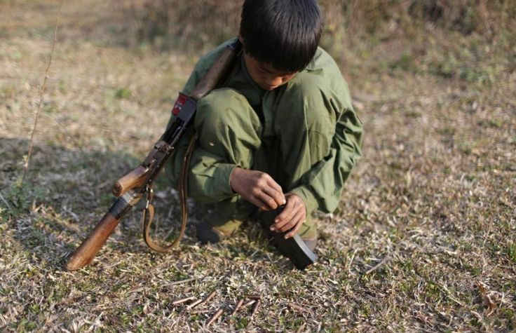 A 15-year-old rebel soldier of the Myanmar National Democratic Alliance Army (MNDAA) inserts bullets into the clip of his rifle near a military base in Kokang region March 11, 2015. Fighting broke out last month between Myanmar's army and MNDAA, which groups remnants of the Communist Party of Burma, a powerful Chinese-backed guerrilla force that battled Myanmar's government before splintering in 1989. REUTERS/Stringer