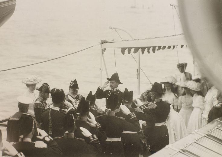 Rei Edward VII, Nicolau II, Imperador da Rússia e Rainha Alexandra estão de pé para a esquerda. Rei Edward VII e Nicholas II estão vestindo uniforme naval cerimonial. Grã-duquesa Olga Nikolaevna, Grã-duquesa Tatiana Nikolaevna, Grã-duquesa Maria Nikolaevna e Grã-duquesa Anastasia Nikolaevna estão em um grupo para a direita, junto com a mãe Imperatriz Alexandra Feodorovna. No deck entre eles há um grupo de oficiais da Marinha em trajes cerimonial, todos saudand. Junho de 1909.