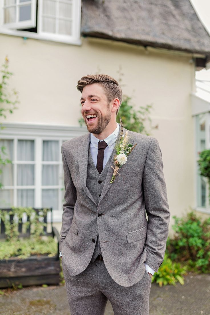 Groom wears a three piece grey tweed suit. Photography by Kerrie Mitchell.