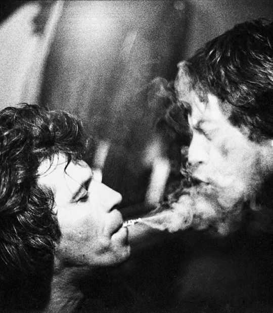 Keith Richard blowing smoke into Mick Jagger's mouth, 1981.