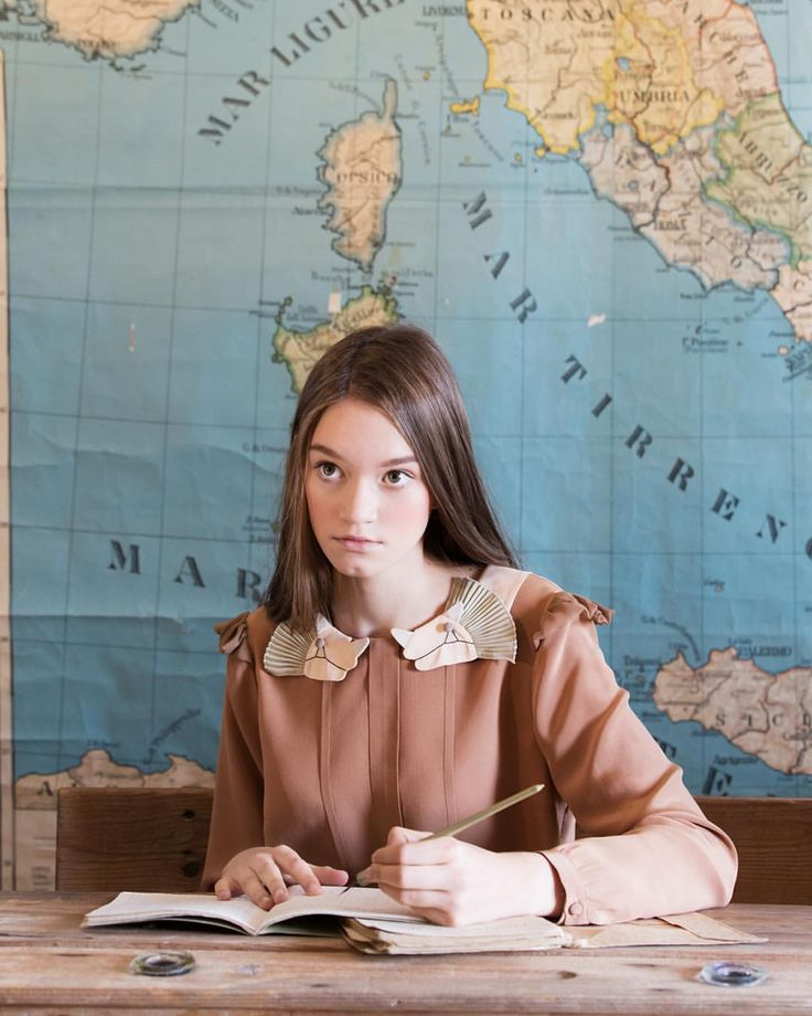 I love the collar on her tan dress and the giant wall map behind.