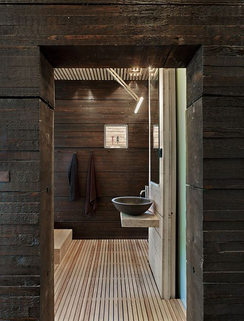 For a simple, wood-lined bathroom and sauna in Sweden, a refined fixture byArne Jacobsenfor Vola does the trick.  Photo by: James Silverman