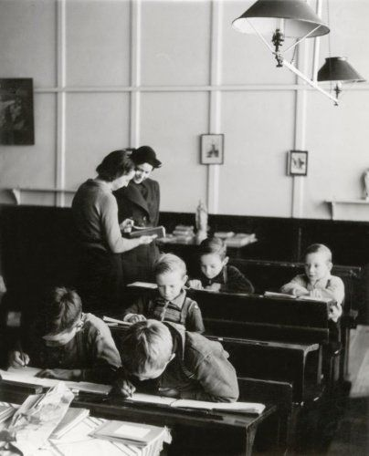 Justitie, politie, kinderbescherming, Nederland. Reportage over de Haagse kinderpolitie op controle. Controle van kinderen: zijn alle leerplichtigen naar school? Den Haag ('s-Gravenhage), januari-maart 1940. De kinderen zitten in de schoolbanken in het klaslokaal waarin nog gaslampen (gasverlichting) hangen.