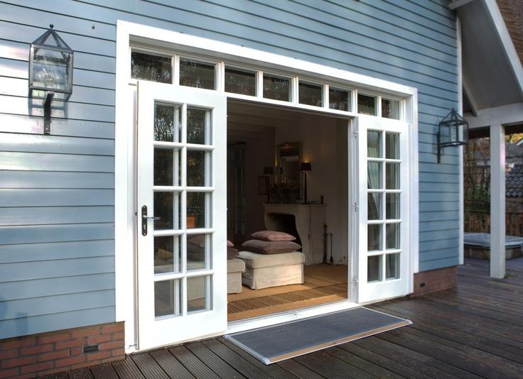 Terras van een Scandinavische villa met haard. Dit prachtige huis krijgt door zijn mooie grijsblauwe kleur een Scandinavisch uiterlijk. De witte openslaande deuren steken hier mooi bij af. Door de handige plaatsing van de deurmat verminder je het ingelopen vuil aanzienlijk, wat de houten vloer binnen zeker ten goede komt. De deurmat is van RiZZ en heeft een teak-afwerking.